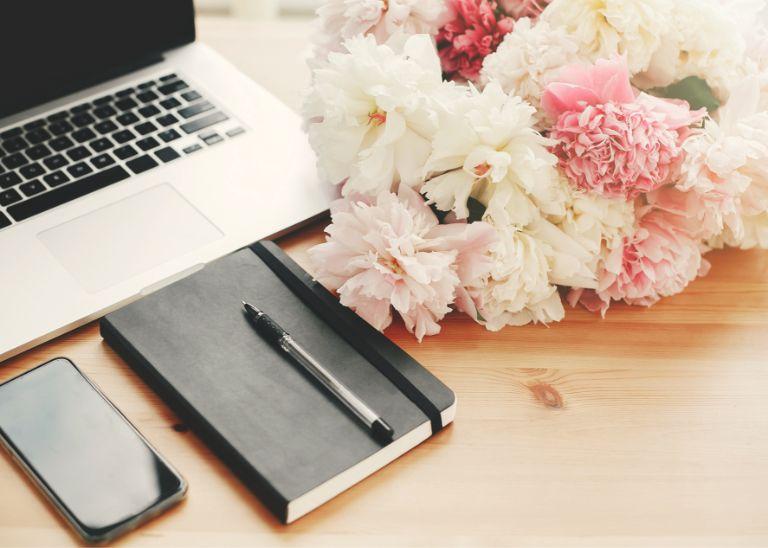 kwiaty leżące obok laptopa